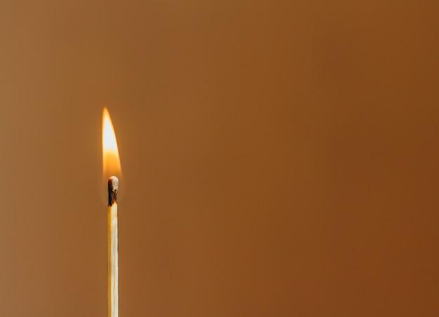 Brennendes streichholz auf undeutlichem braun
