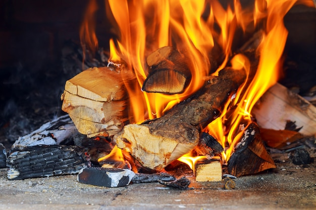 Brennendes und glühendes stückholz im kamin