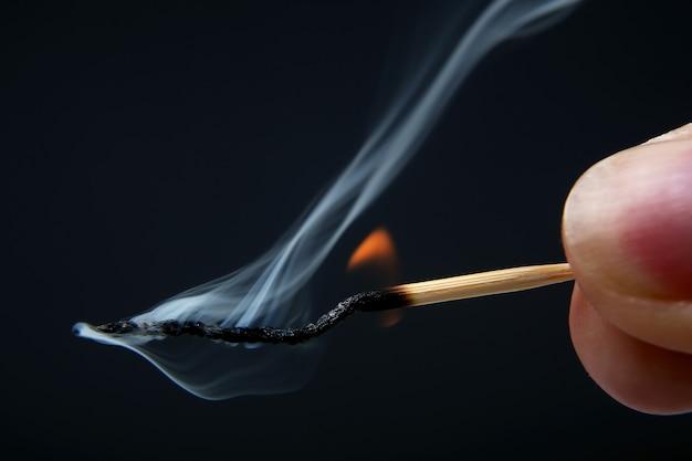 Brennendes und rauchendes hölzernes streichholz in der hand auf dunkelheit