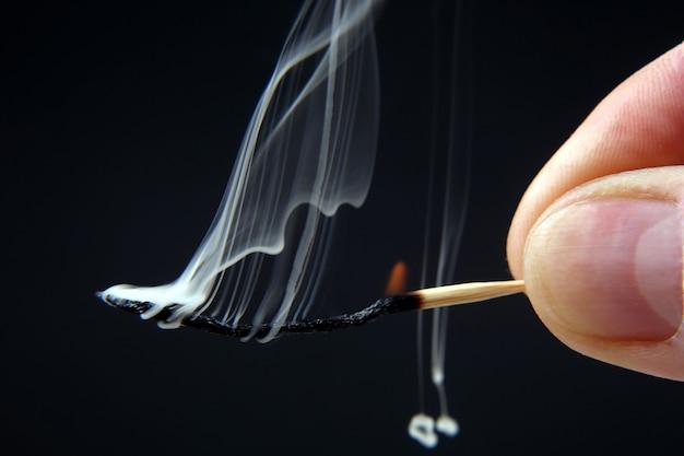 Brennendes und rauchendes holzstreichholz in der hand auf dunklem hintergrund. feuerquelle