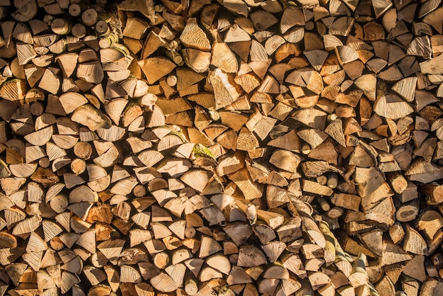 Brennholz an der wand, hintergrund von trockenen gehackten brennholzstämmen in einem stapel.