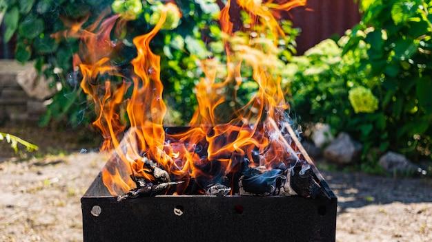 Brennholz brennt im grill. ruhe in der natur. heiße kohlen. lagerfeuer feuer.