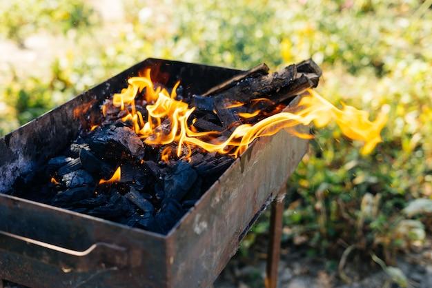 Brennholz brennt in einem grill im hintergrund der natur