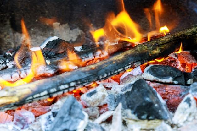 Brennholz, das in einem messingarbeiter auf einer hellen gelben flamme einen baum, dunkelgraue kohlen innerhalb eines metallmessingkessels brennt.