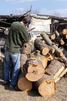 Brennholz für den winter vorbereiten, kirschstämme im hof aufgeschichtet, der bauer bereitet die kettensäge für die arbeit vor
