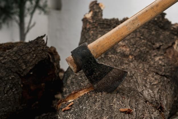Brennholz-hackaxt. axt für einen baum, auf einem baumstumpf. entwaldungskonzept. försteraxt oder zimmermann. klassische axt steckt in einem baumstamm. kofferraum abschneiden