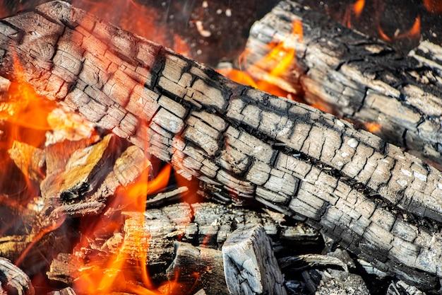 Brennholz und kohlen im grill verbrennen. brennendes feuer. fleisch grillen. kohlen zum braten.