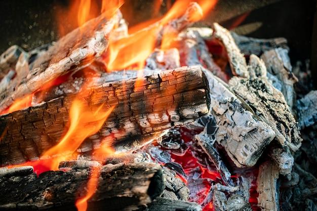 Brennholz und kohlen im grill verbrennen. nahansicht. makroaufnahmen. brennendes feuer. fleisch grillen.