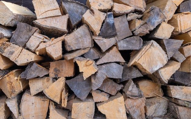 Brennholz zum heizen des ofens, gestapelt in einem holzstapel.