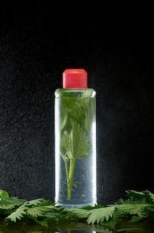 Brennnesseln in einer klaren plastikflasche und wasserstaub