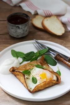 Bretonische buchweizencrepes mit ei, spinat und sahne, zusammen mit dem kaffee. rustikaler stil.