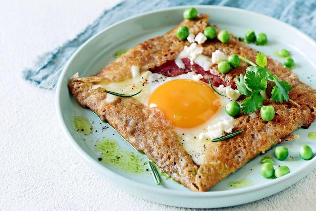 Bretonischer traditioneller pfannkuchen aus buchweizenmehl mit schinken, käse, ei, feta, erbsen und grüner butter.