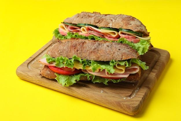 Brett mit ciabatta-sandwiches auf gelbem hintergrund