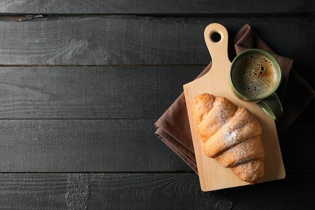 Brett mit croissant und tasse kaffee auf hölzernem hintergrund, draufsicht