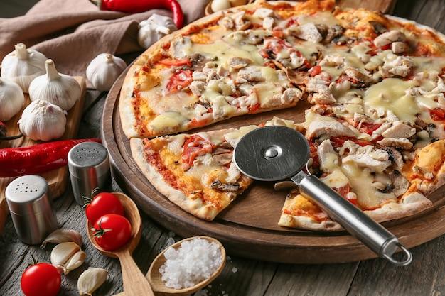 Brett mit der leckeren pizza auf hölzernem hintergrund