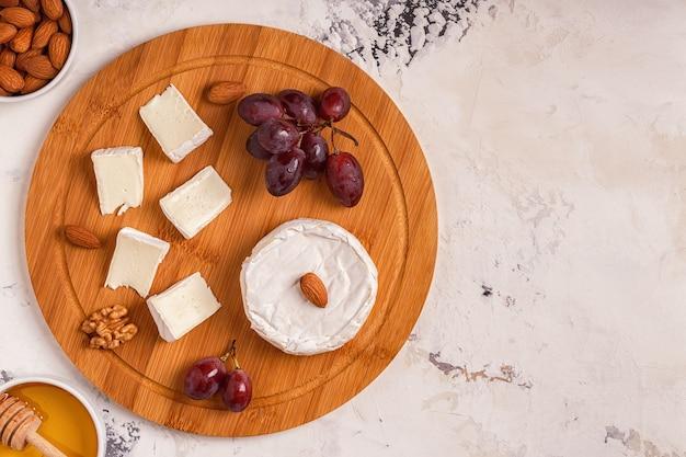 Brett mit käse, trauben, nüssen und honig