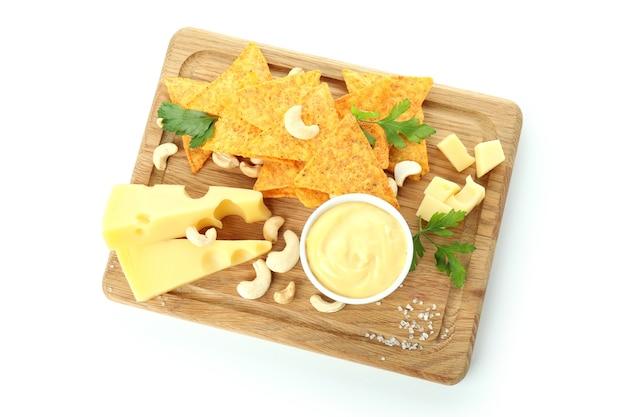Brett mit käsesauce und snacks auf weißem hintergrund