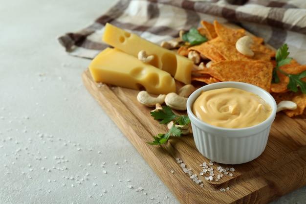 Brett mit käsesauce und snacks auf weißem strukturiertem tisch