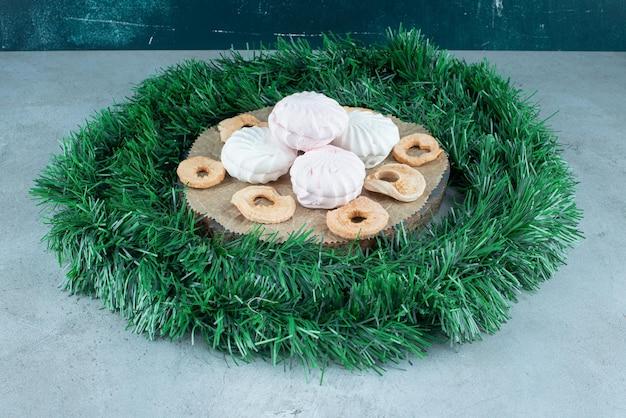 Brett mit keksen und trockenen apfelscheiben in einem girlandenkreis auf marmor.