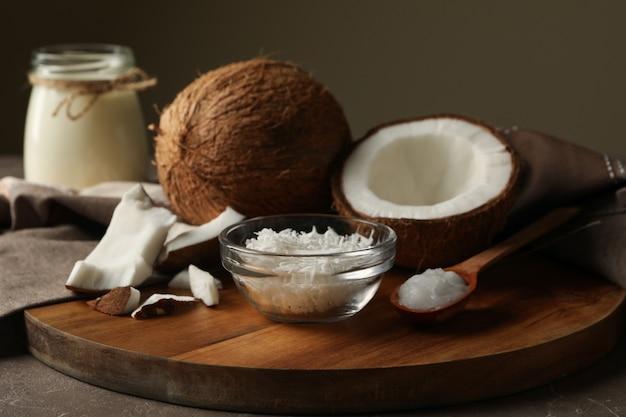 Brett mit kokosnuss und kokosflocken auf grauem tisch