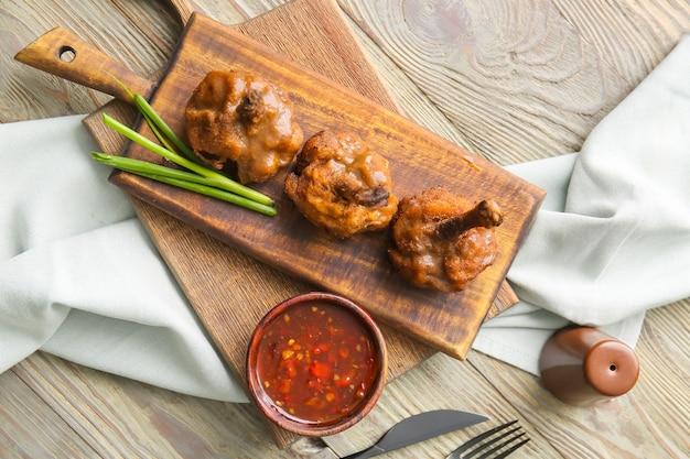 Brett mit leckeren hühnerlutschern und sauce auf holzoberfläche
