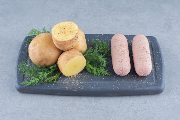 Brett mit leckeren würstchen, kartoffeln und gemüse auf holzbrett.