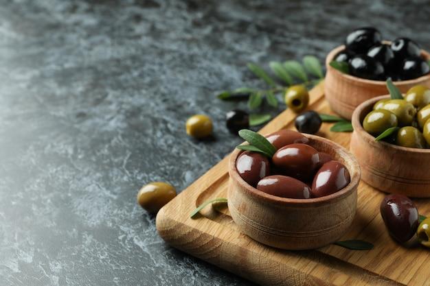 Brett mit oliven und blättern auf schwarzem rauchigem hintergrund