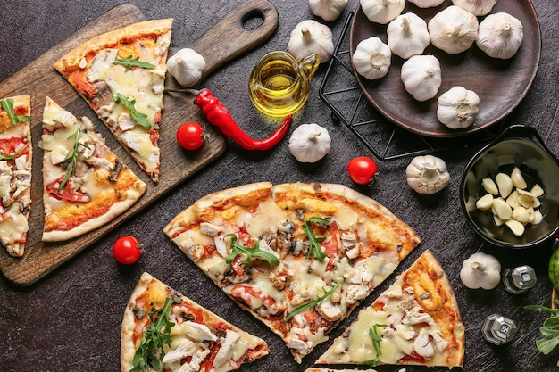 Brett mit scheiben der leckeren pizza auf dunklem hintergrund