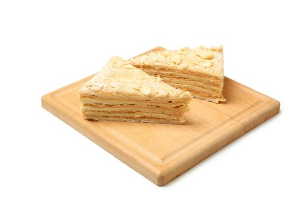 Brett mit stücken des napoleon-kuchens lokalisiert auf weißer oberfläche