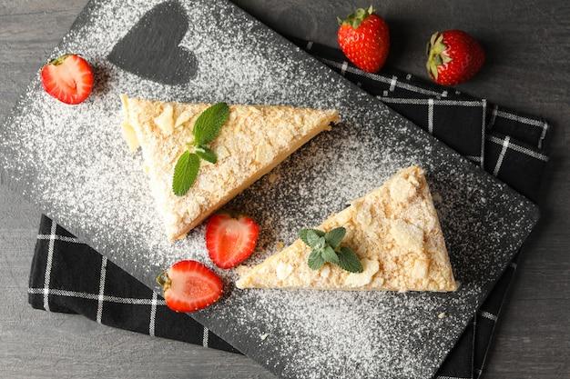 Brett mit stücken napoleon-kuchens mit erdbeere auf schwarzer oberfläche