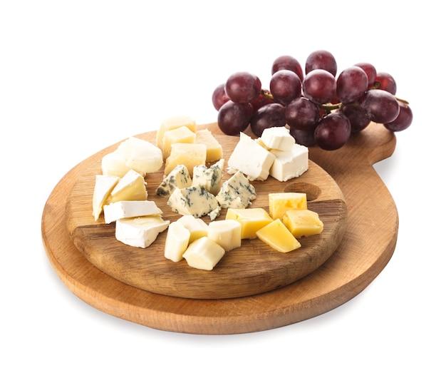 Brett mit stücken von verschiedenen käsesorten und trauben, isoliert auf weiß