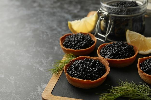 Brett mit törtchen und glas mit kaviar auf schwarzem rauch