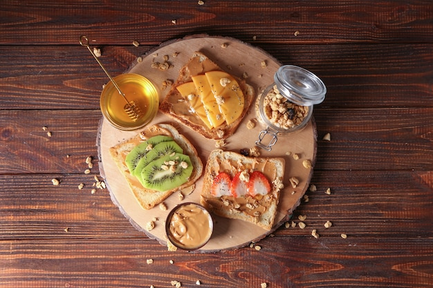 Brett mit verschiedenen leckeren toasts und honig auf holztisch