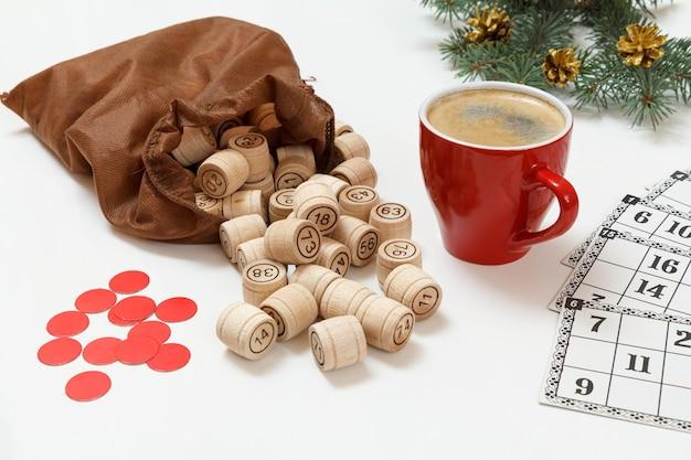 Brettspiel lotto. hölzerne lottofässer mit brauner tasche, spielkarten, roten chips und einer tasse kaffee, weihnachtstannenzweige im hintergrund