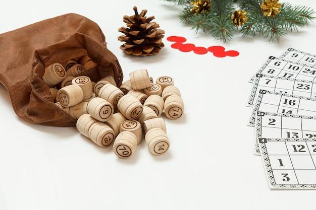 Brettspiel lotto. hölzerne lottofässer mit brauner tasche, spielkarten und roten chips für ein spiel im lotto, weihnachtstannenzweige im hintergrund. geringe schärfentiefe