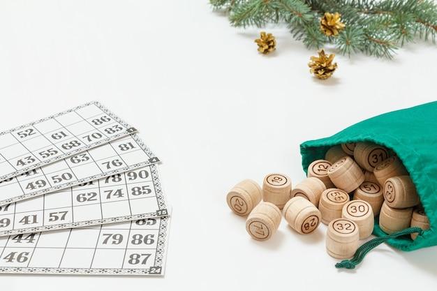 Brettspiel lotto. lottofässer aus holz mit grüner tasche und spielkarten. weihnachtstannenzweige im hintergrund. geringe schärfentiefe