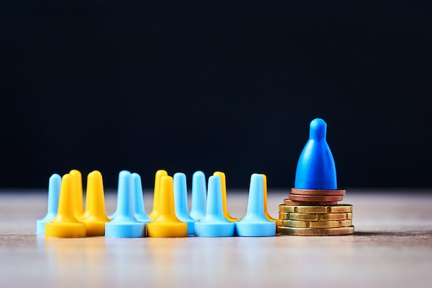Brettspielfigur auf haufen münzen und menge aus den anderen figuren