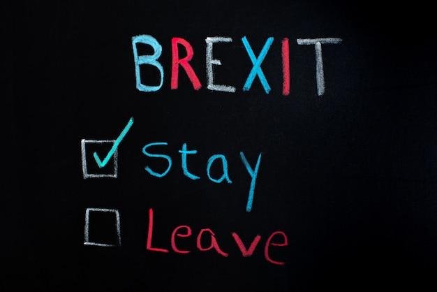 Brexit-konzept, wahl zwischen bleiben oder verlassen, auf tafel geschrieben.