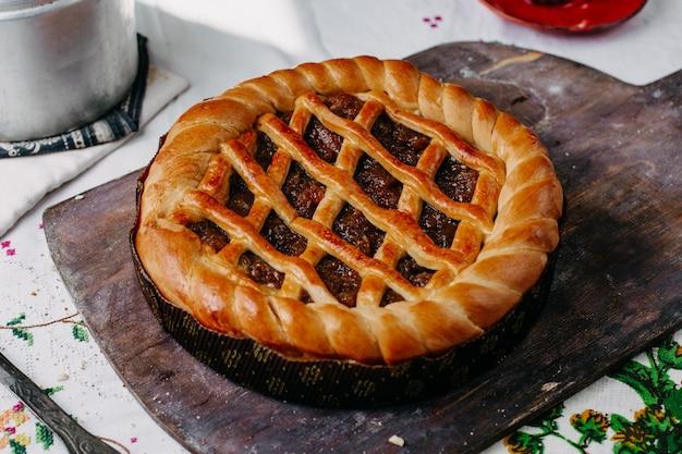 Brezel geformter kuchen mit schokolade rund gebacken süß lecker braun in runden pfanne auf braunem holz schreibtisch