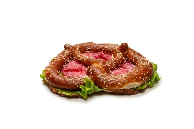 Brezel mit salami und salat auf einem weißen hintergrund. leckerer imbiss.
