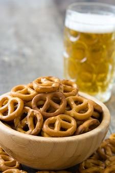Brezeln in der schüssel und im bier auf holztisch