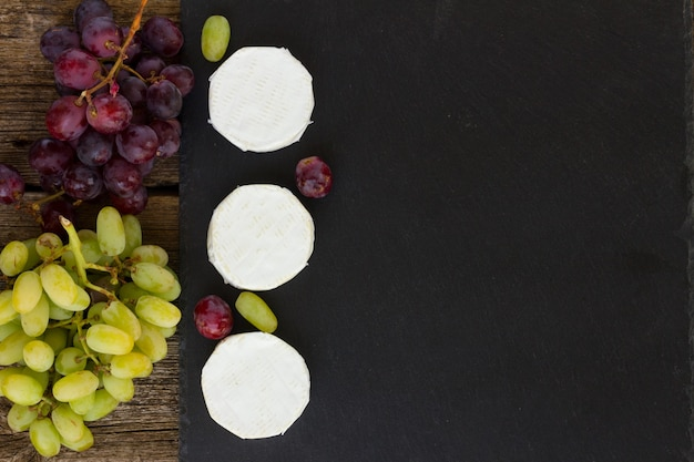 Brie-käse auf schwarzem schneidebrett mit roten und weißen trauben, kopierraum