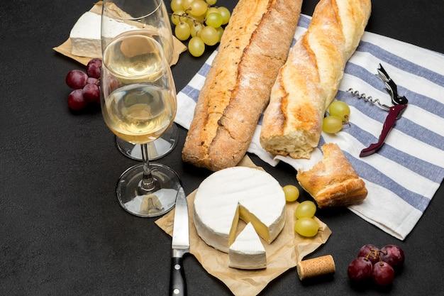 Brie-käse, baguette und zwei gläser weißwein auf dunklem betonhintergrund