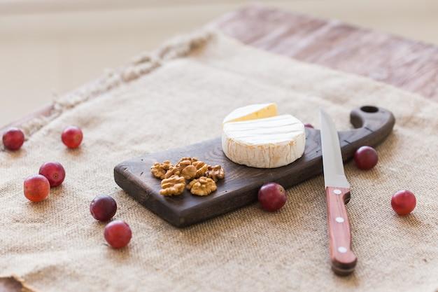 Brie oder camembertkäse mit nüssen und trauben auf einem holzbrett