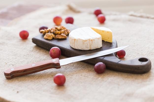 Brie oder camembertkäse mit nüssen und trauben auf einem holzbrett.