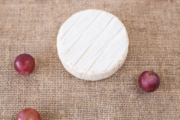 Brie oder camembertkäse mit trauben auf rustikalem hintergrund draufsicht