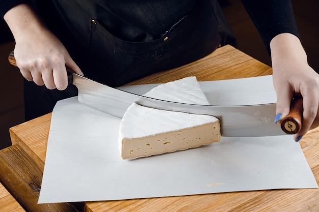 Brie weicher weißkäse aus kuhmilch. brie auf dem holztisch schneiden. bio leckeres essen.