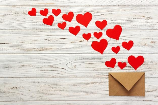 Brief an den valentinstag. liebesbriefumschlag mit roten herzen auf holz