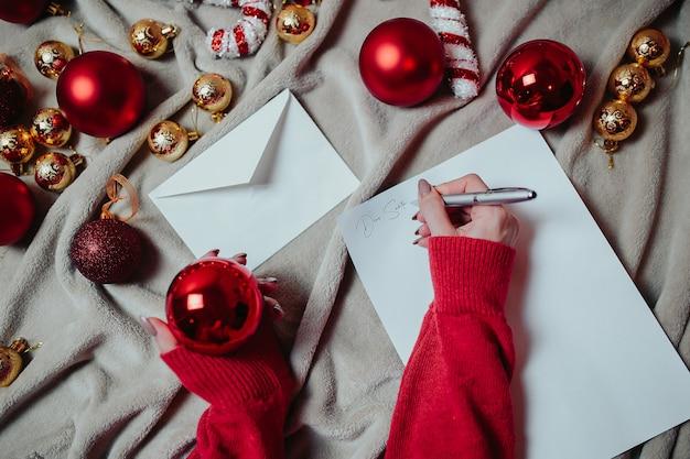 Brief an den weihnachtsmann. flache lage mit roten weihnachtskugeln, goldenen weihnachtskugeln und weihnachtszuckerstangen auf dem plaid.