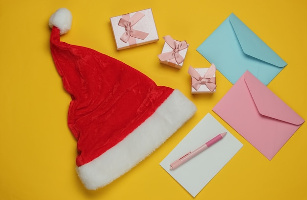 Brief an den weihnachtsmann. weihnachtsmütze, umschlag mit brief und stift, schachteln mit geschenken auf gelbem hintergrund. weihnachtswohnung lag. draufsicht Premium Fotos